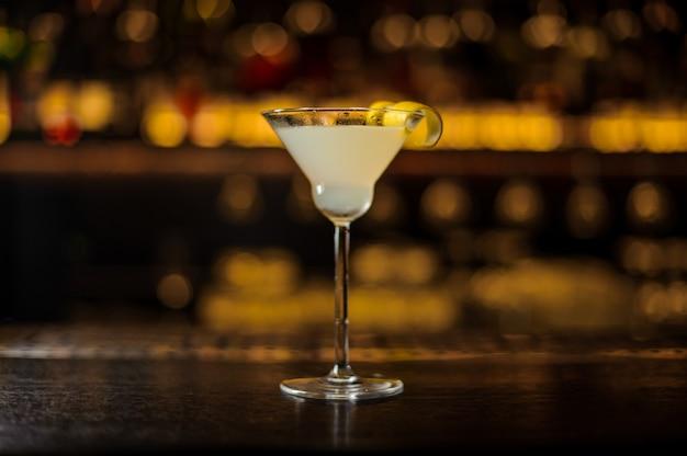Bicchiere da cocktail con cocktail fresco aspro e dolce decorato con buccia d'arancia contro le luci dorate