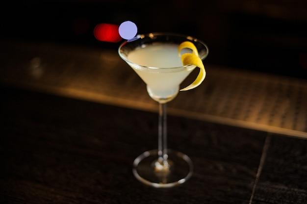 Bicchiere da cocktail con cocktail fresco aspro e dolce decorato con buccia d'arancia sullo sfondo scuro