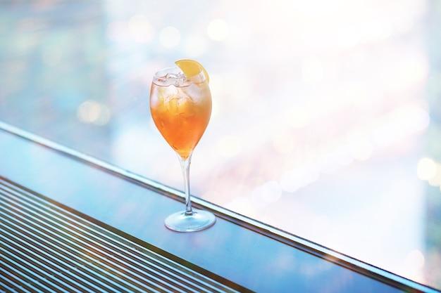Bicchieri da cocktail sul davanzale della finestra vicino al vetro di un edificio alto
