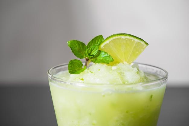 Succo di cocktail con lime, menta e ghiaccio. accessori per bevande da bar su sfondo nero da tavola.