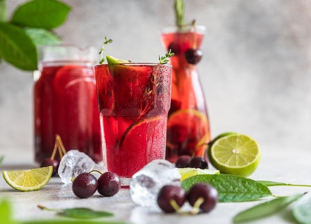 Cocktail o limonata con ciliegie e lime, sfondo pietra grigia. analcolico. bevanda estiva fredda.