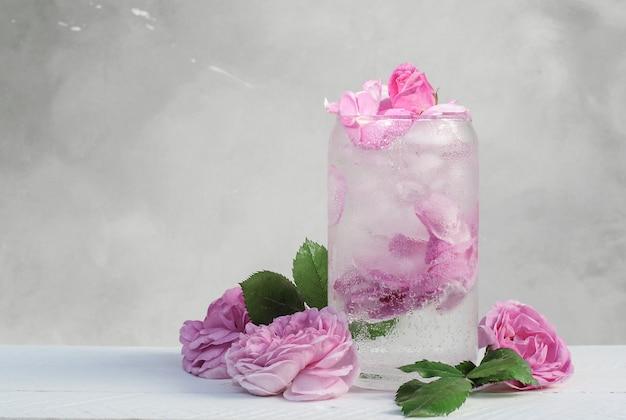 Cocktail di cubetti di ghiaccio di petali di rosa rosa chiaro su uno sfondo grigio con fiori di rosa