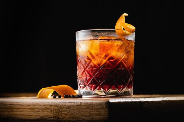 Cocktail negroni su una vecchia tavola di legno.