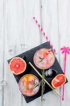 Cocktail con la fetta di pompelmo su una tavola di legno
