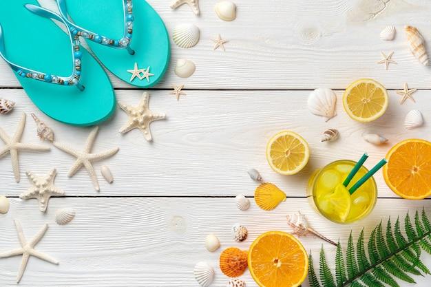 Cocktail con ghiaccio, arance, limoni, conchiglie, stelle marine e infradito su uno sfondo di legno chiaro.