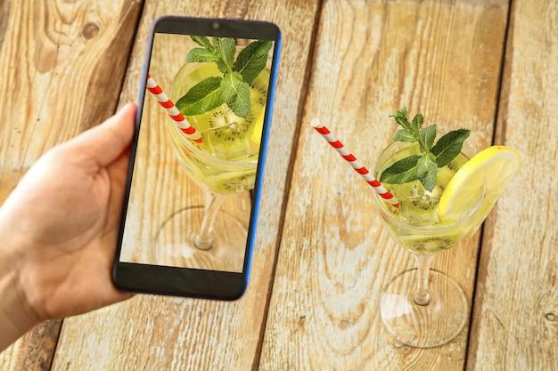 Cocktail con kiwi menta e limone in un bicchiere su un tavolo di legno. la mano femminile prende le immagini.