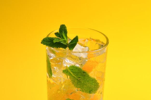 Cocktail con limone e menta su sfondo giallo. copia spazio.
