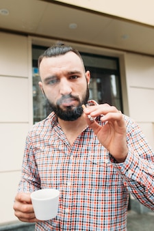 Presuntuoso hipster con caffè e ritratto di sigaretta