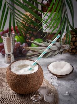 Cocktail coco loco su un tavolo da bar con cubetti di ghiaccio, coperchio di cocco, alcuni frutti sullo sfondo con foglie di palma