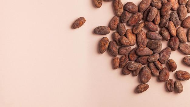 Fave di cacao su una superficie rosa