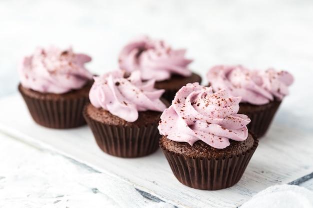 Cupcakes al cacao decorati con crema di bacche e cioccolato