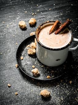 Bevanda al cacao con zucchero scuro cinnamonnd sul nero sul tavolo rustico.