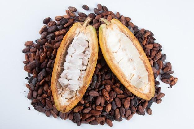 Frutta di cacao tagliata con fave di cacao crude su sfondo bianco.