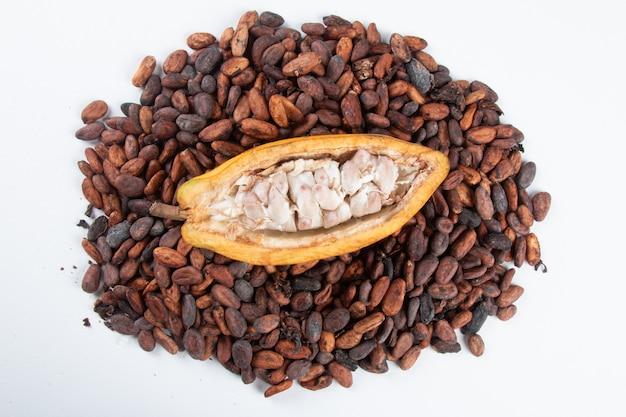 Frutta di cacao tagliata con fave di cacao crude su un bianco.
