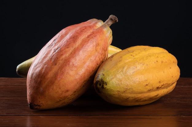Frutto di cacao isolato sul tavolo con il nero.