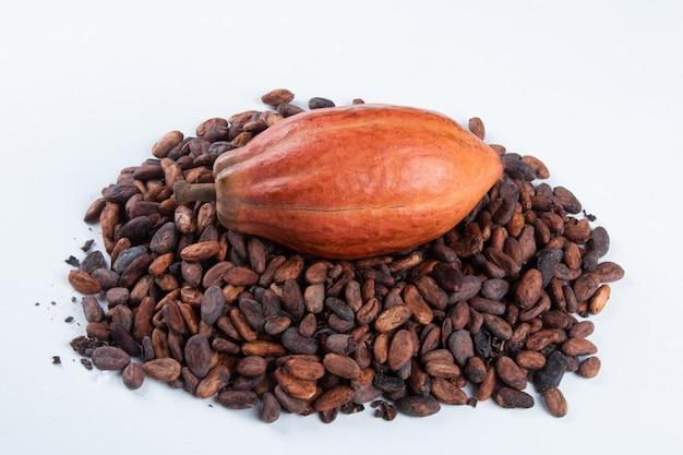 Frutta del cacao sopra le fave di cacao crude su bianco. Foto Premium