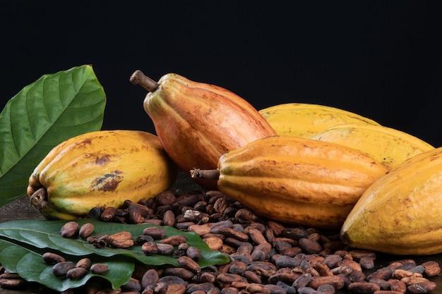 Frutti di cacao e fave di cacao crude sul tavolo con sfondo nero.