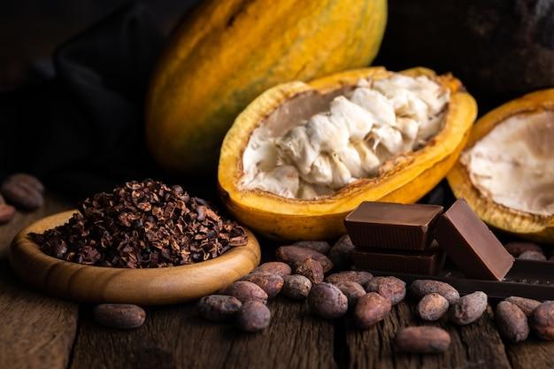 Baccelli di cacao, fagioli e polvere sul tavolo di legno, vista dall'alto