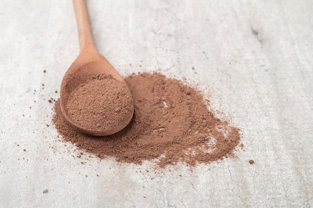 Cacao in polvere su un cucchiaio di legno su sfondo rustico.