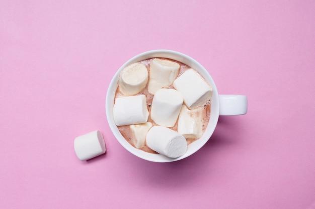 Cacao con marshmallow in una tazza di ceramica bianca su sfondo rosa