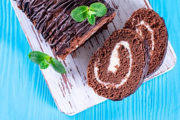 Rotolo di cioccolato con ripieni bianchi su sfondo blu. cibo dolce del deserto