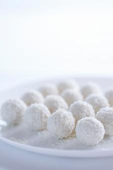 Torte al cocco dessert leggero sotto forma di palline su sfondo chiaro