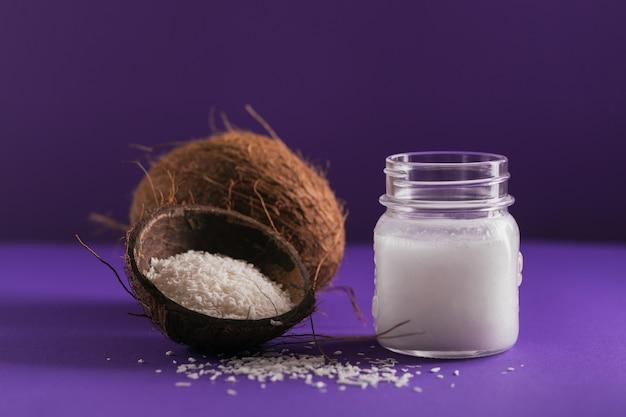 Cocco, fiocchi di cocco e olio di cocco in vaso su sfondo viola. concetto di cucina sana
