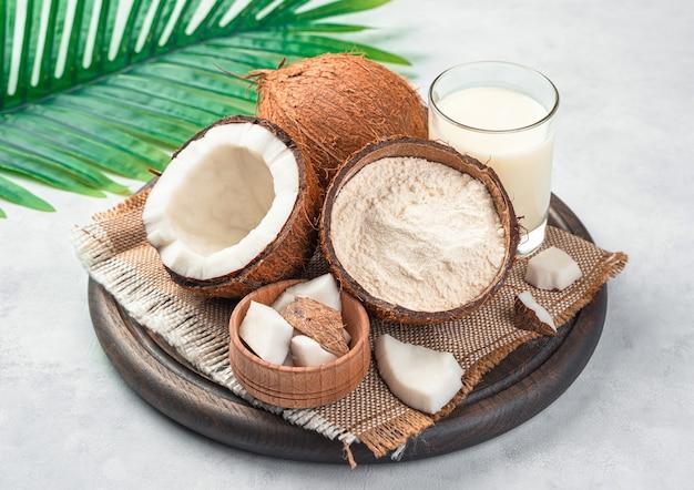 Cocco, farina di cocco e latte su sfondo grigio. sostituti sani del latte vaccino a base vegetale e farine senza glutine.