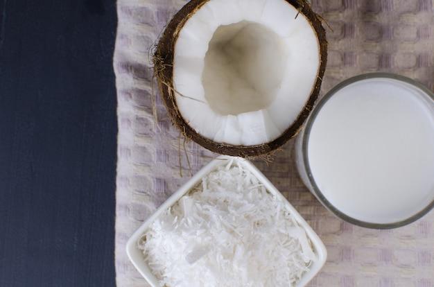 Cocco, trucioli di cocco e latte di cocco su sfondo nero.