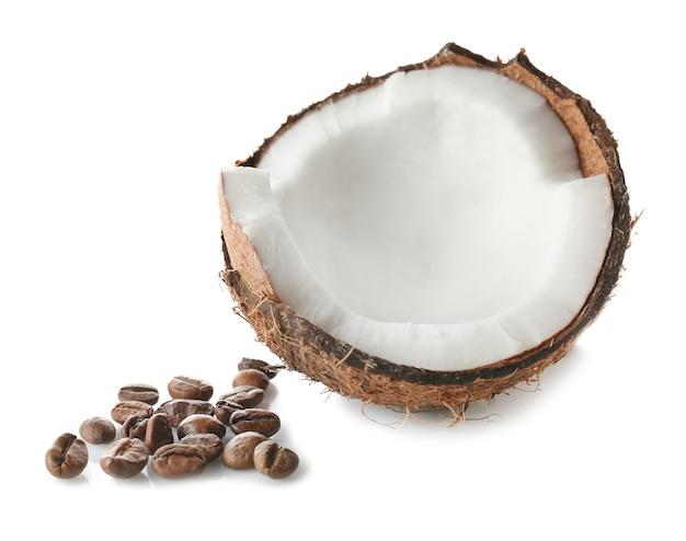 Noce di cocco e chicchi di caffè su sfondo bianco