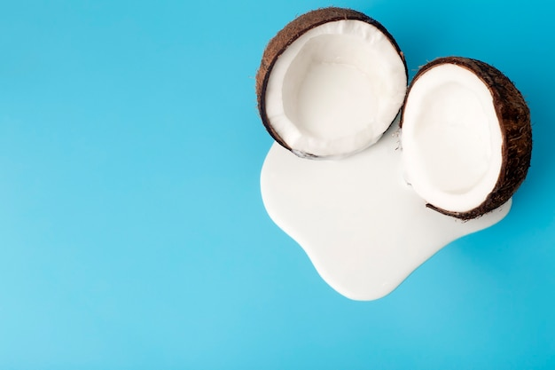 Crema di cocco o burro con noci di cocco fresche su sfondo blu. succo di panna bianca che gocciola dal cocco.