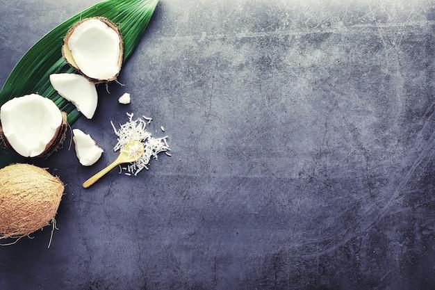 Cocco su un tavolo di pietra scura. olio di cocco e cucchiaio.