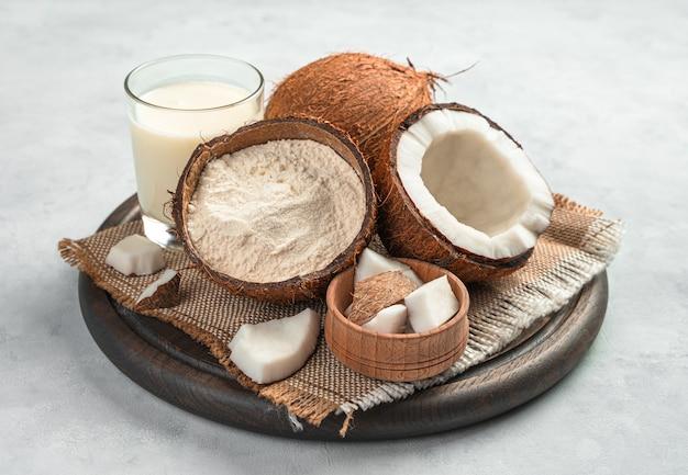 Farina di cocco, latte di cocco e cocco fresco aperto su sfondo grigio. vista laterale, primo piano.