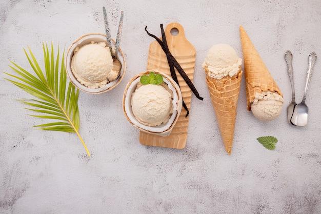 Gusti di gelato al cocco a metà della configurazione di cocco su pietra bianca.