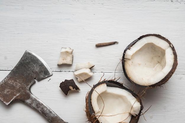 Una noce di cocco viene tagliata a metà su un tavolo di legno chiaro vista dall'alto