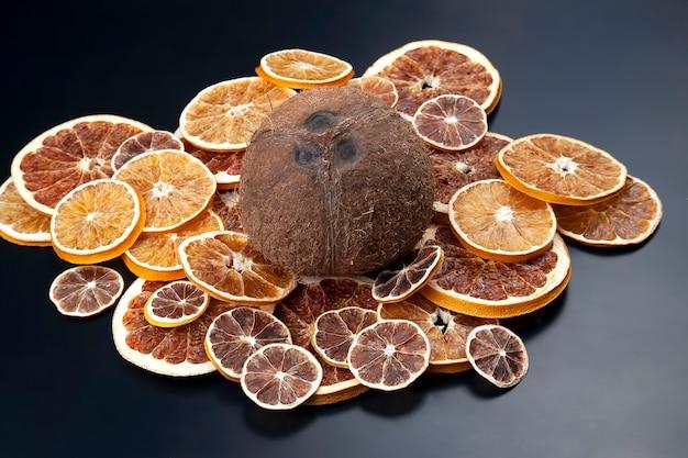 La noce di cocco si trova tra gli agrumi secchi su uno sfondo scuro