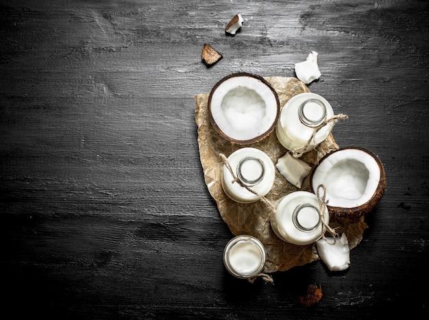 Latte di cocco in bottiglia. su uno sfondo di legno nero.