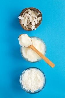 Olio di cocco, patatine al cocco e scaglie di cocco sulla superficie blu. prodotti naturali. vista dall'alto. copia spazio. posizione verticale.
