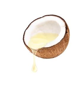 Olio di cocco che gocciola da frutti di cocco tagliati a metà isolati su sfondo bianco.
