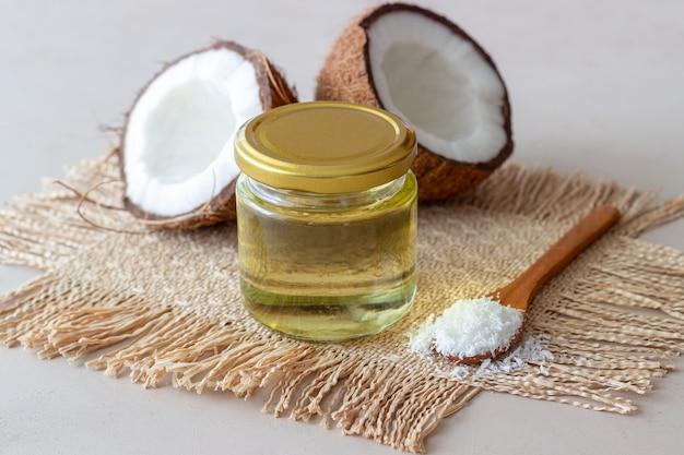 Olio di cocco in un barattolo e noci di cocco fresche su una superficie beige. cosmetici naturali.