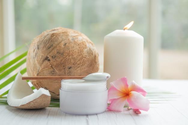 Olio di cocco, foglie tropicali e noci di cocco fresche. prodotti spa cocco su superficie in legno chiaro.