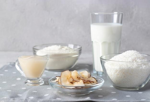 Prodotti a base di cocco: scaglie di cocco, farina, latte, latte condensato e patatine su sfondo grigio chiaro. mangiare sano