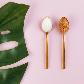 Cocco e zucchero bianco raffinato in cucchiai d'oro su una superficie rosa