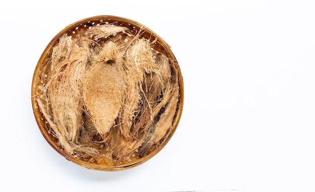 I capelli delle coperture della noce di cocco per la piantatura sul canestro di trebbiatura di bambù di legno su bianco