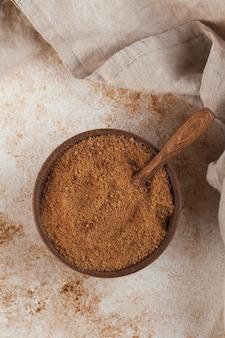 Zucchero di cocco in una ciotola di legno con una foglia di palma