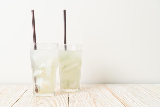 Acqua di cocco o succo di cocco in bicchiere con cubetto di ghiaccio