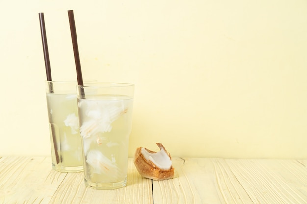 Acqua di cocco o succo di cocco in bicchiere con cubetto di ghiaccio Foto Premium