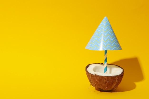 Noce di cocco con l'ombrello di spiaggia sulla tavola gialla