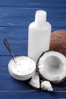 Cocco con caramelle al cocco e olio di cocco fresco su fondo di legno blu
