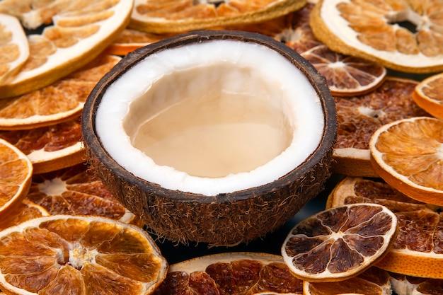 Noce di cocco con latte naturale su uno sfondo di agrumi secchi
